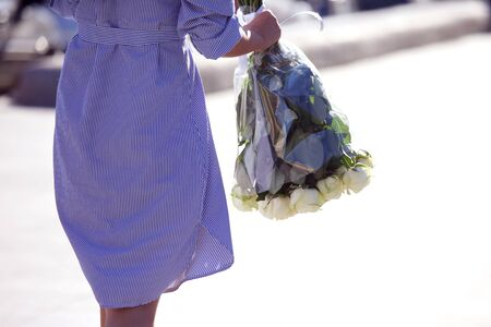 girl in a blue striped dress comes with a bouquet of white roses