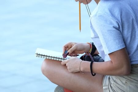 girl draws in a notebook sitting on the pavement