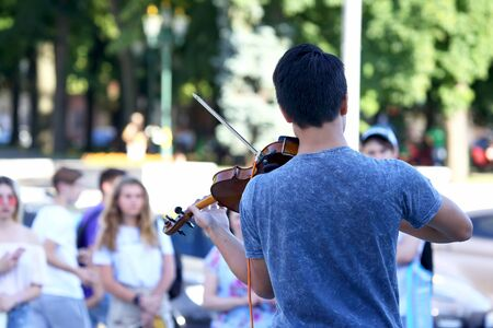 guy plays violin for street people