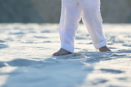 bare feet of a child in white pants on the sand