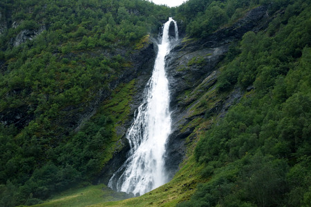 large waterfall in mountainous and wooded areas