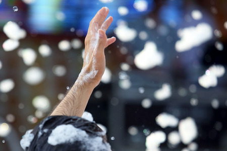 raised hand of a man in soap foam at a concert