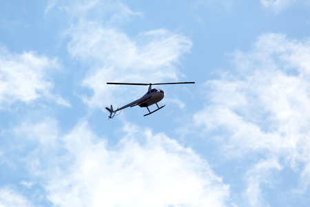 The helicopter flies in the sky