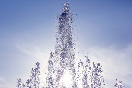 sunlight breaks through the falling waters of the fountain Stock Photo