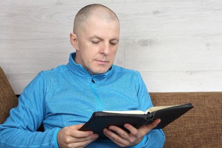 man sitting on sofa and reading a book of the Bible