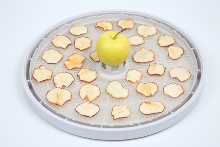 Dried Apple slices on trays of special electric fruit dryer