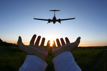 raised hands on the background of a passenger plane flying at sunset Foto de archivo