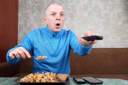 the man eats rice pilaf and stares of TV program