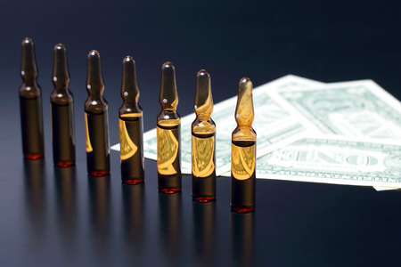 seven medical glass ampoules for injection on the background of dollar banknotes Stock fotó