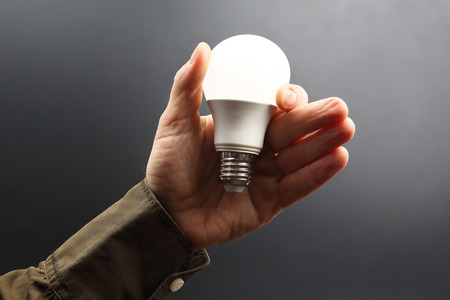 Included led new lamp in human hand on dark background