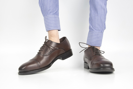 Classic brown shoes worn on the hands on a white background Stock Photo