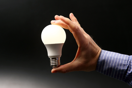 human hand holding the included led lamp on a dark background 写真素材