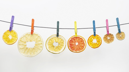 dried pieces of citrus fruits hang on clothespins on white background