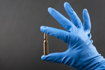 medical injection ampule in blue gloved hand