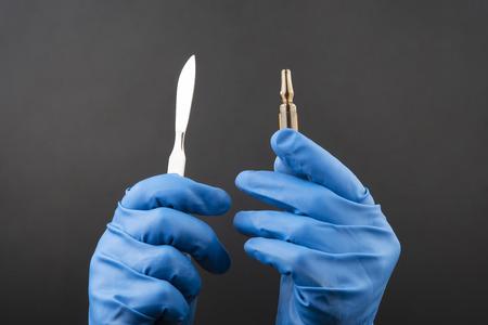 Medizinisches Skalpell und Durchstechflasche zur Injektion in den Händen mit blauen Handschuhen Standard-Bild