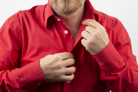 Bearded man takes off undress red shirt