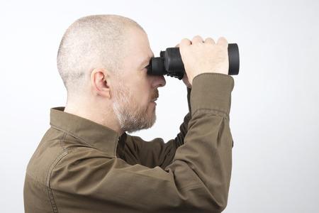 Bearded man with binoculars in his hands looking