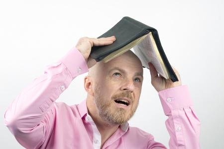 Bearded man in a pink shirt hides his head under an open Bible