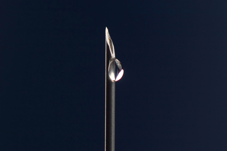 close-up of a drop of medicine on the tip of a medical injection needle