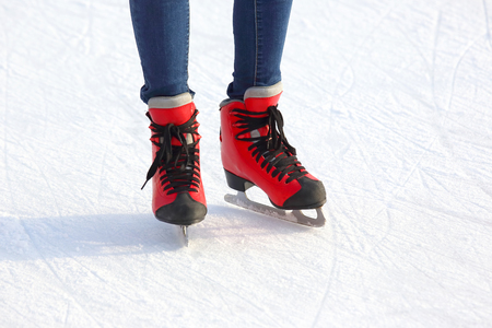 Female legs in skates on an ice rink