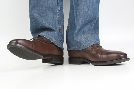 Male legs in jeans and brown classic shoes on white background Stock Photo