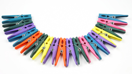 Colored plastic clothespins for clothes on a white background