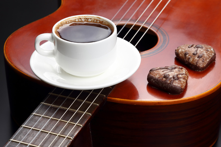 white cup with black coffee and cookies lying on the acoustic guitar