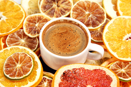 Dried slices of various citrus fruits and black coffee in a white Cup Imagens