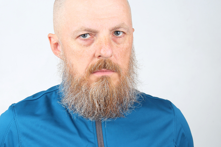 portrait of a serious bearded man in a blue sports jacket