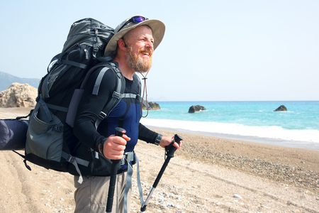 bearded traveler with a backpack on the beach enjoys the beautiful scenery