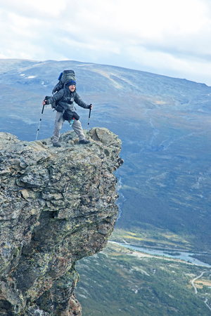 Man traveler with a backpack stands on a rocky ledge in the highlands