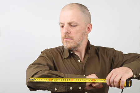 man measures the length of his elbow centimeter