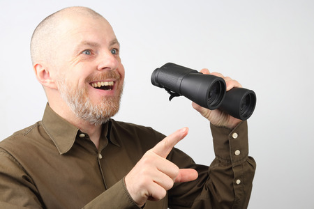 bearded man with binoculars in his hands happy to look into the distance