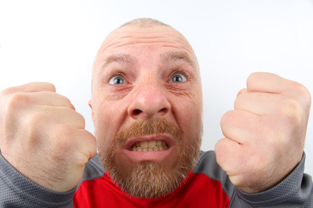 Bearded man with strong emotions and with clenched fists closeup on white background