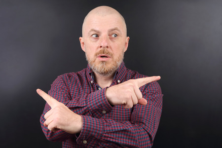 portrait of a man pointing his index fingers in different directions Stock Photo