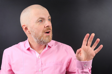 surprised bearded man in a pink shirt with his hand raised Stock Photo