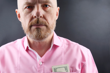 Bearded man in a pink shirt  money in his pocket Stock Photo