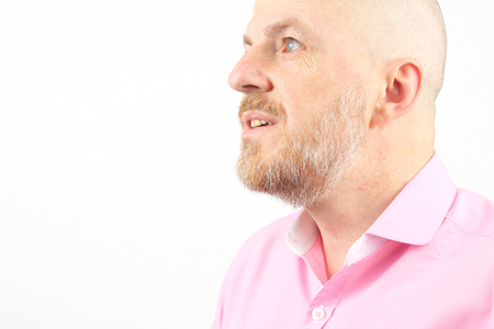 Studio portrait of a bearded man in a pink shirt