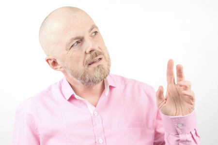 bearded man in a pink shirt with his hand raised Stock Photo