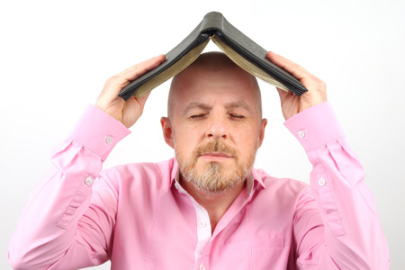 Bearded man covers his head with an open Bible Stock Photo