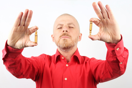 man in a red shirt is holding two vials for injection Stock Photo