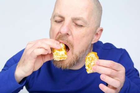 bearded man in a blue sweater eating a honeycomb