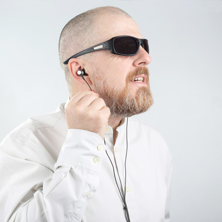 bearded man with sunglasses listening music in headphones compact