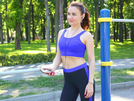 cute young sporty girl listening to music on a walk