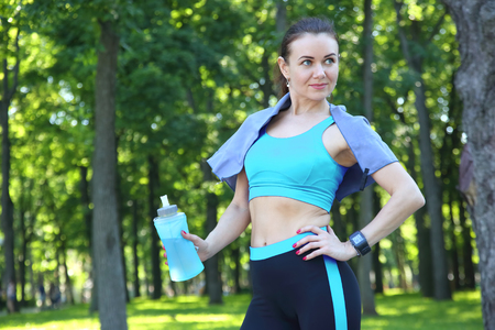 young sporty girl drinking water from a bottle