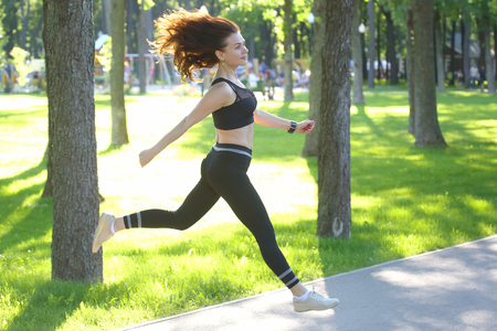 cute young sporty girl in jump running at a distance Stock Photo