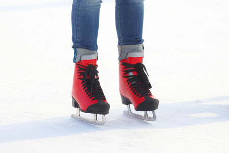 feet in red skates on an ice rink