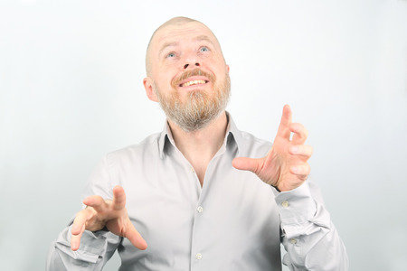 Bearded man with raised hands looking up