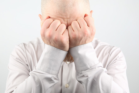 sad man with hands closed face on white background
