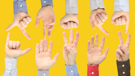 Various gestures of male hands between each other on a yellow background. Sign language relations in society. Discussion and understanding your opponent with your hands